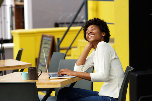 African american woman laughing with laptop at cafe